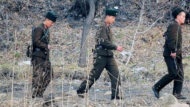 This file photo shows North Korean soldiers patrolling along the bank of the Yalu River in the North Korean town of Sinuiju across from the Chinese city of Dandong.